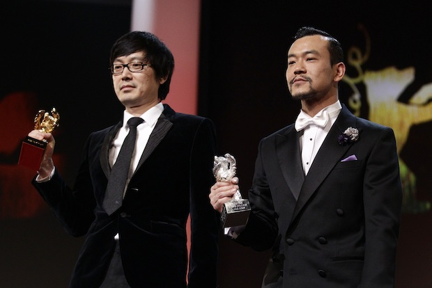 Actor Liao Fan and director Diao Yinan pose with Silver Bear for Best Actor and Golden Bear for Best film during awards ceremony of 64th Berlinale International Film Festival in Berlin